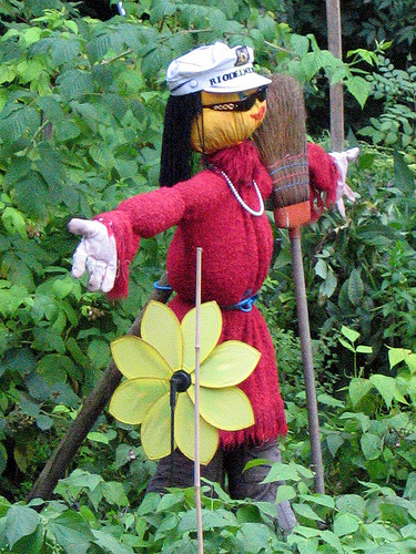 Female scarecrow carrying a broom in a garden