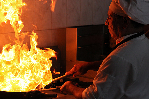 Restaurant resume owning chef in kitchen, hot flames from pan