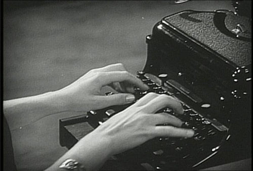 secretary typing on a typewriter