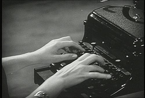 secretary typing on a typewriter